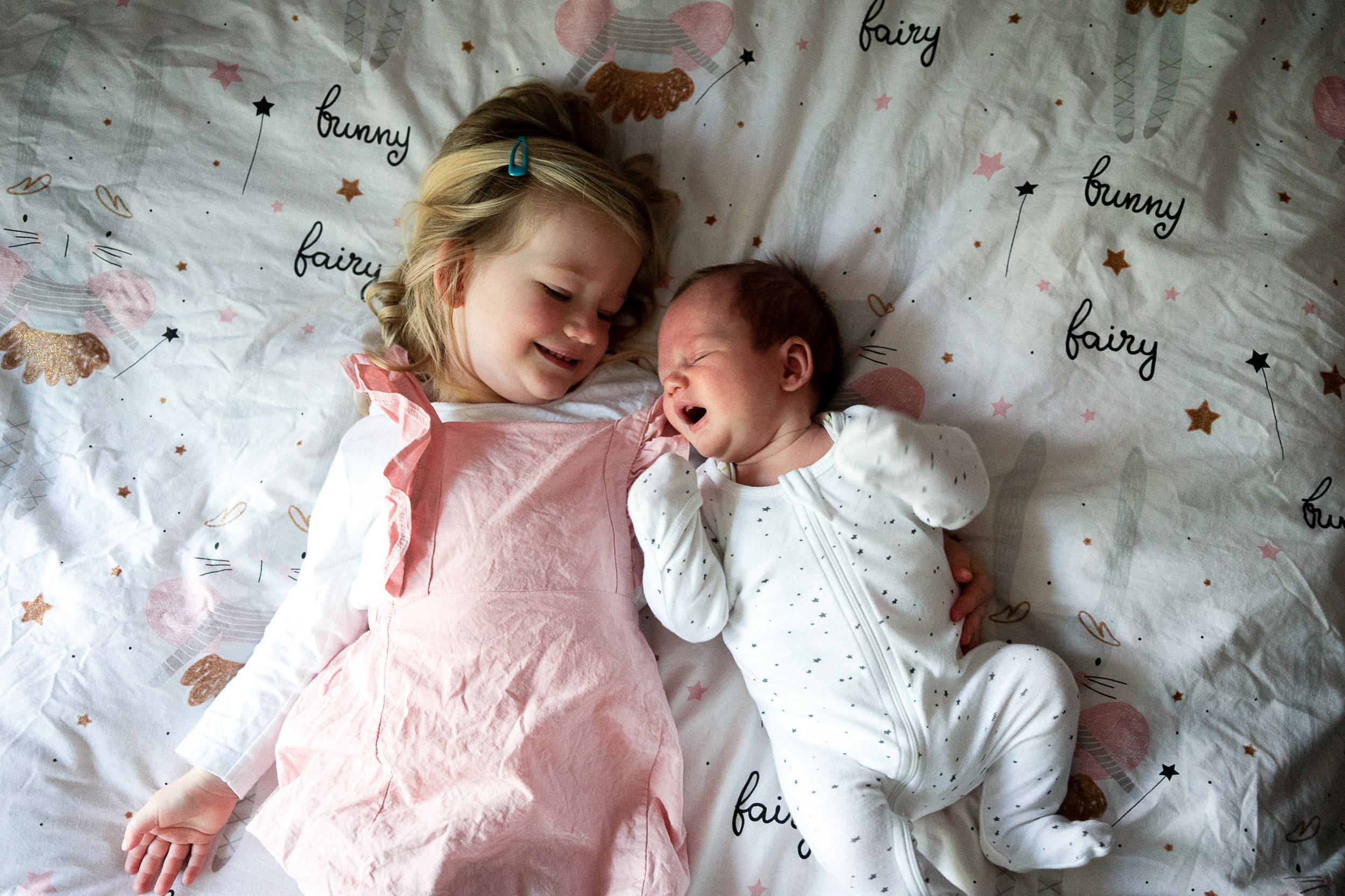 Newborn baby with his older sister on her bed in the sun. Relaxed in-home newborn photography gold coast without props