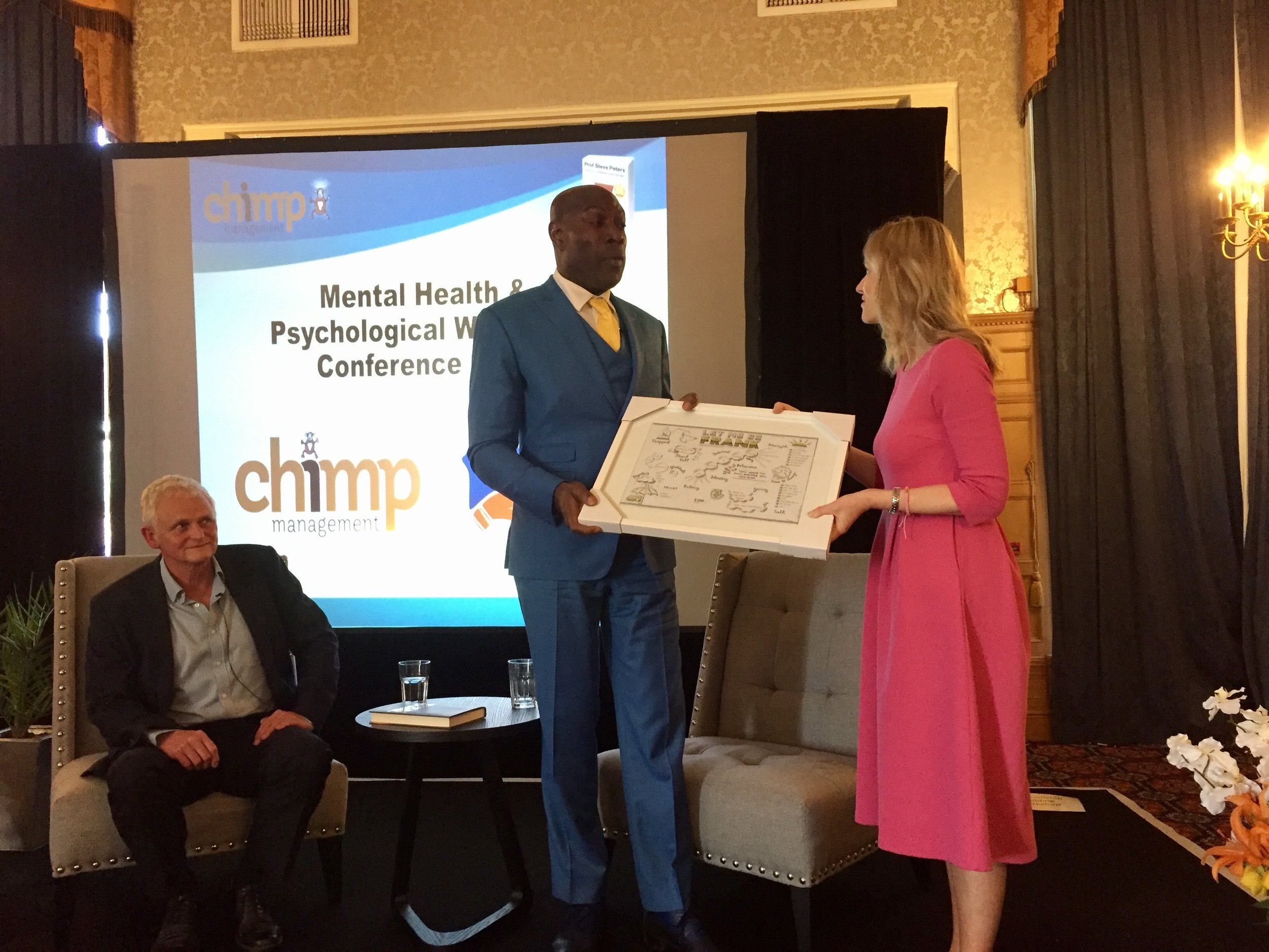 Dani presenting former world heavyweight champion Frank Bruno MBE with a framed VS of his book  Let Me Be Frank  at the Chimp Management Mental Health and Wellbeing Conference. Picture includes Dr Steve Peters, author of  Chimp Paradox