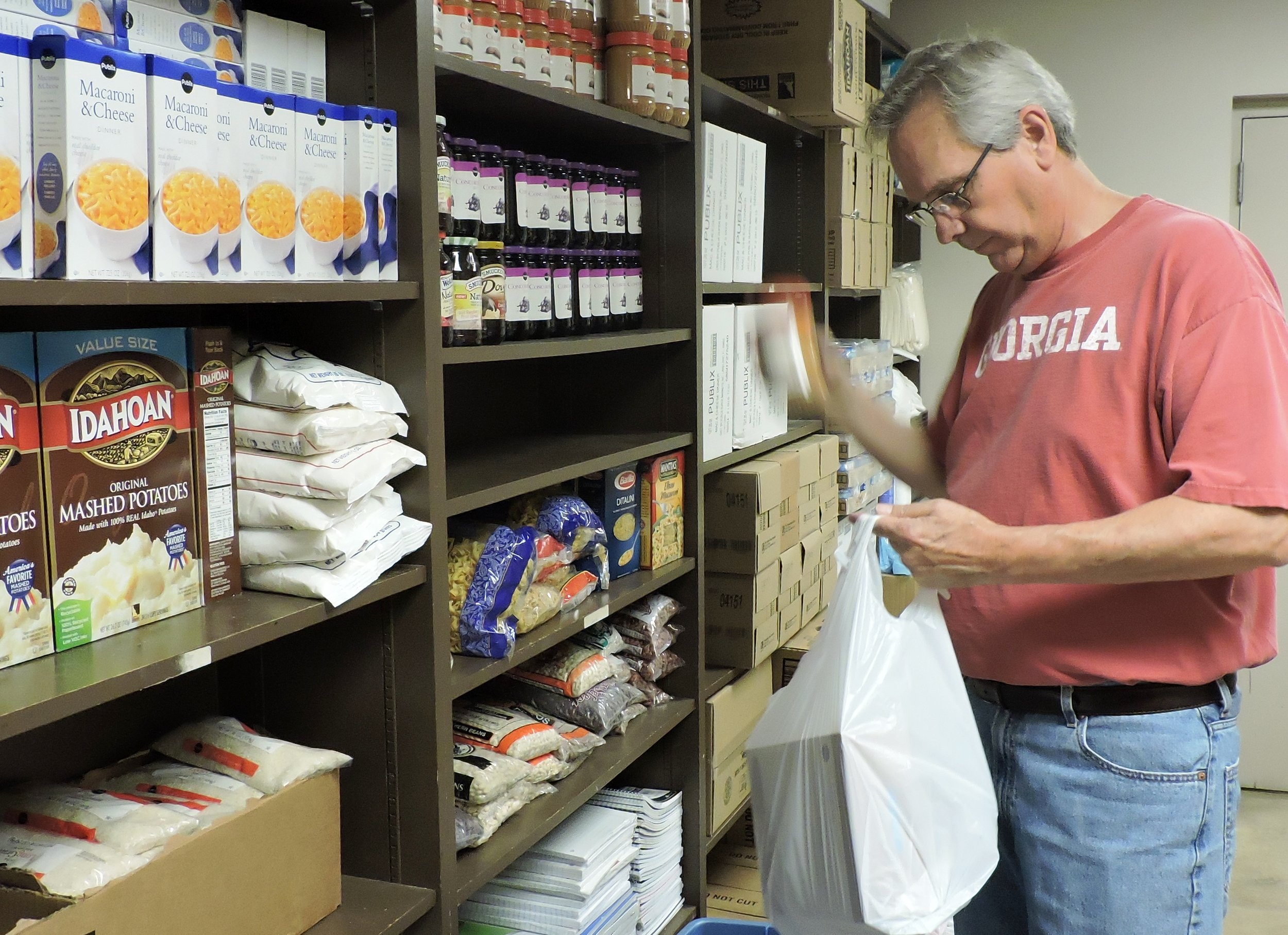Volunteer Phil Collins packs food bags.jpg
