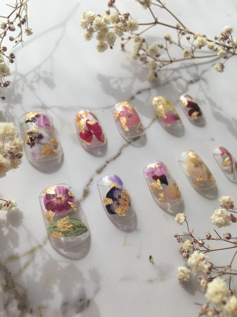 floral press-on nails - How utterly gorgeous are these?! Channel your inner Goddess of nature with dried pressed flower decals and gold or silver flakes. Better yet, for the same cost as a single mani, they're reusable.£35.88