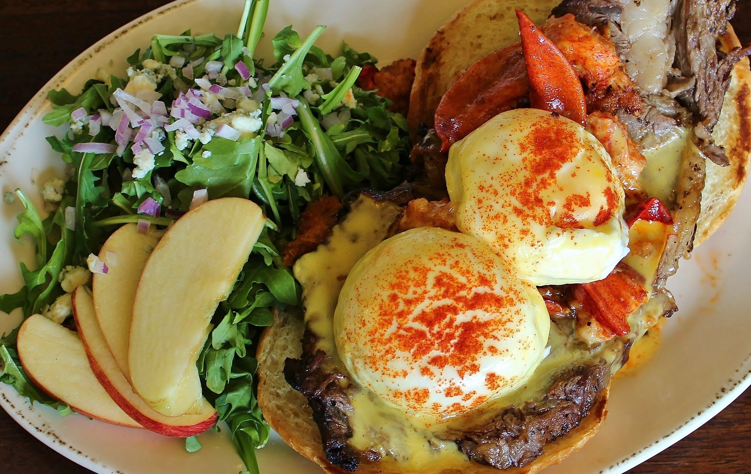 Surf & Turf Benedict - Toasted Croissant with Lobster Claw Meat & Prime Rib (medium rare) topped with Champagne Hollandaise. With choice of side; Tots, Arugula Salad, or Fruit$17.99