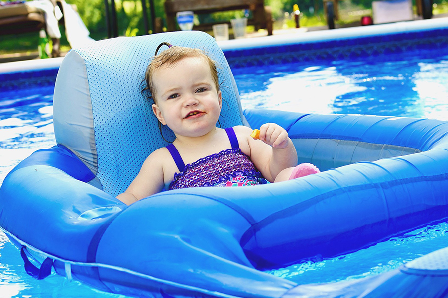 little baby eating a snack on a pool raft
