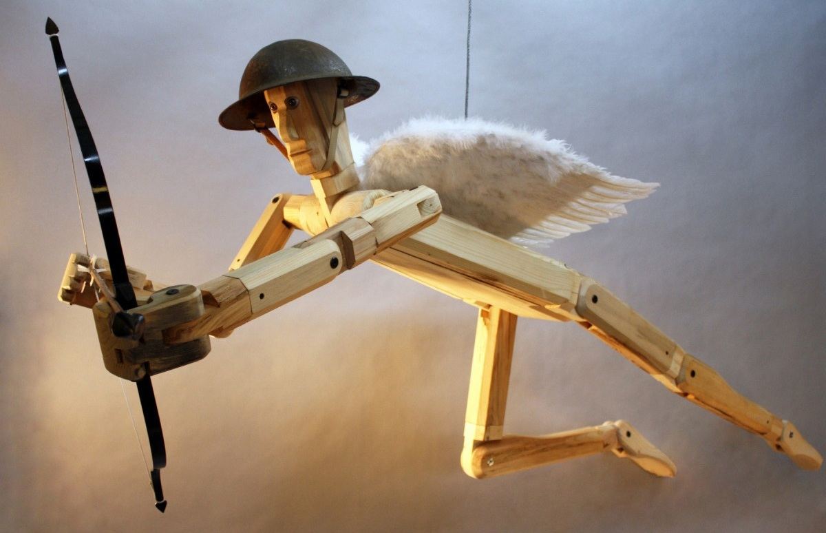 Cupid, Love Drone . 2015. Life-sized. Various reclaimed soft woods, purchased wings, Gaboon ebony arrowhead, WWI field doctor's helmet.