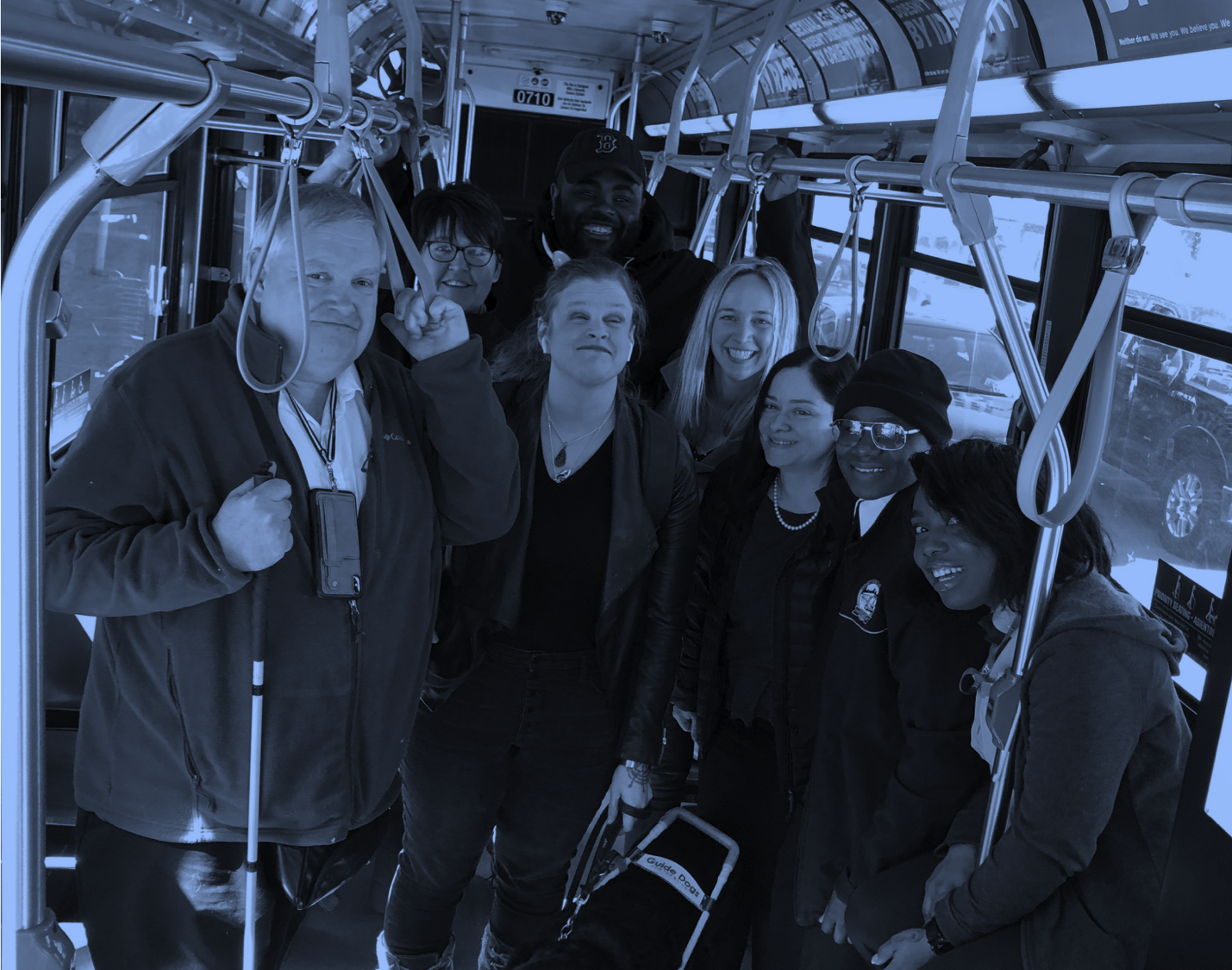 Group of eight people on an MBTA bus smiling with a black dog. The people in the photo worked hard to transform the idea of Access AI into reality. Thanks to all!