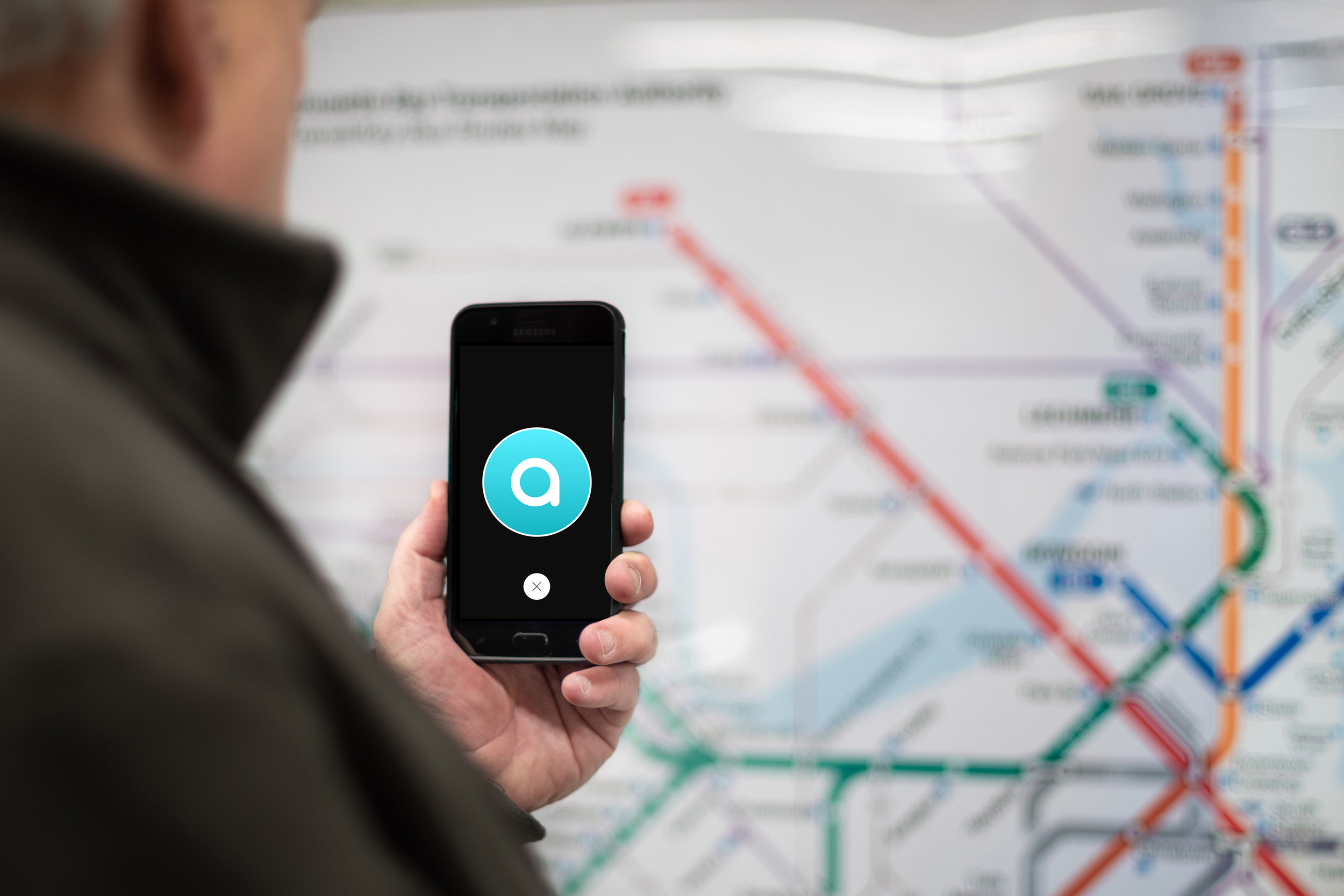 Man holding smartphone in front of MBTA station map. Black phone screen includes turquoise circle outlined in white with the letter a in white centered in the middle.