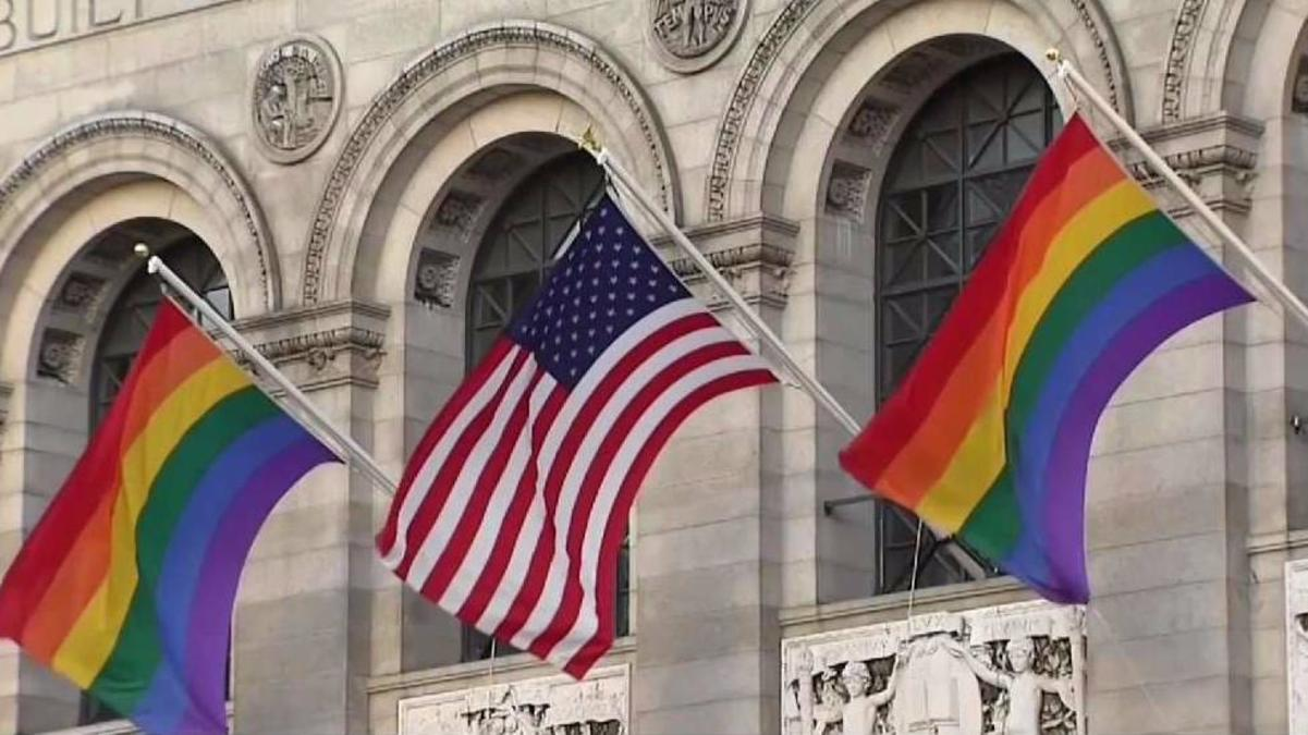 Image Description: Three flags hanging symmetrically between the arched windows of the Boston Public Library. The Rainbow Pride Flags hang to the left and right featuring red, orange, yellow, green, blue and purple stripes. The center flag is of the United States of America and includes 13 red and white stripes along with 50 white stars.