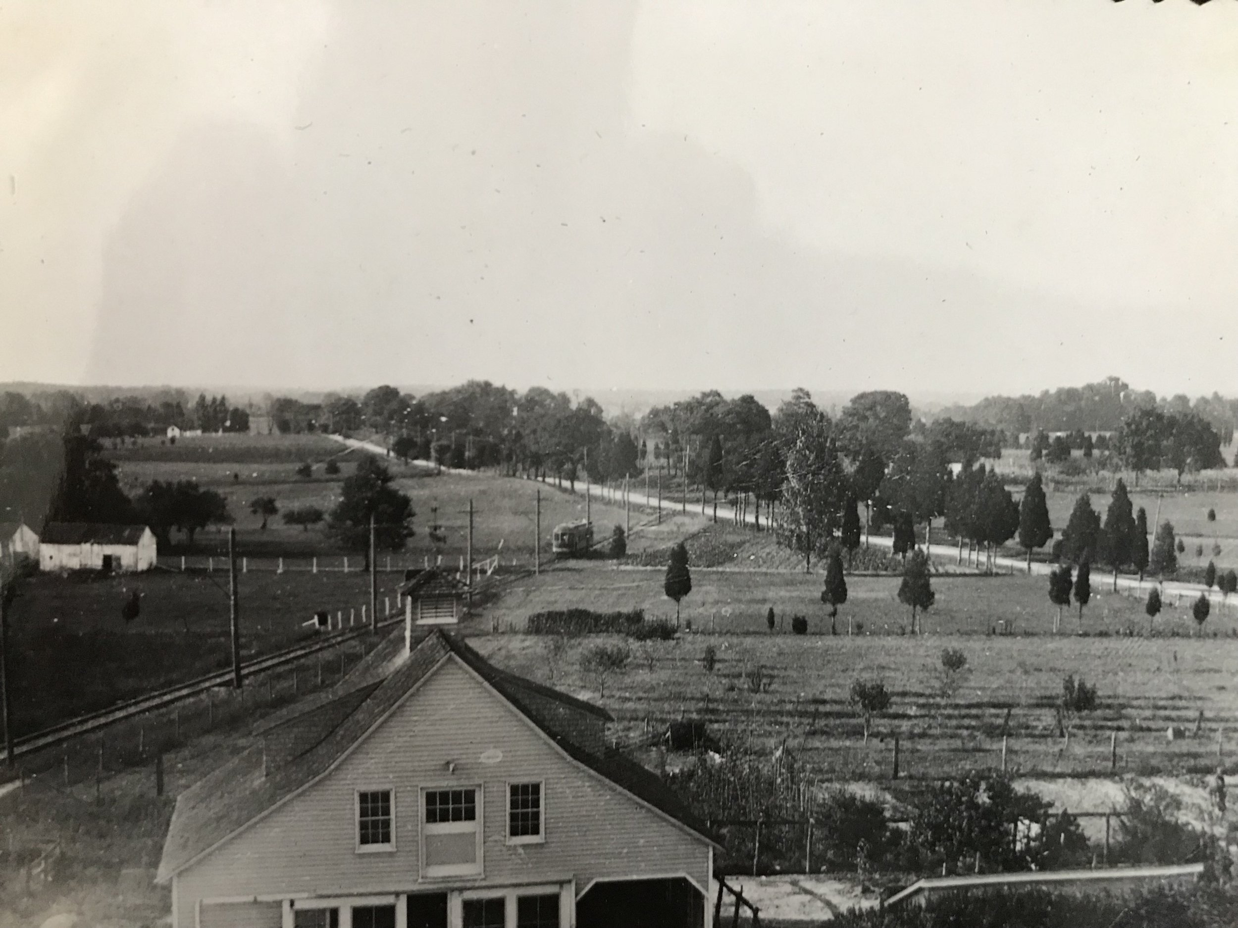 "A trolley heads south from Rockville toward Tenallytown through open farmland. This view appears to be looking north and shows the area south of where Montrose Road intersects with Rockville Pike. The Pike is in the background. The foreground is described by the source as the Villa Roma restaurant (on Wall Lane, where Nicholson Lane is today) — however, although this may be the same house, other sources indicate that the restaurant did not open until about 16 years later (see the discussion of the ""Rainbow Motel"" under the 1960s heading, below). Photo by Lewis Reed, 1910 (courtesy of Reed Bros. Dodge History Blog, https://reedbrothersdodgehistory.wordpress.com/)."