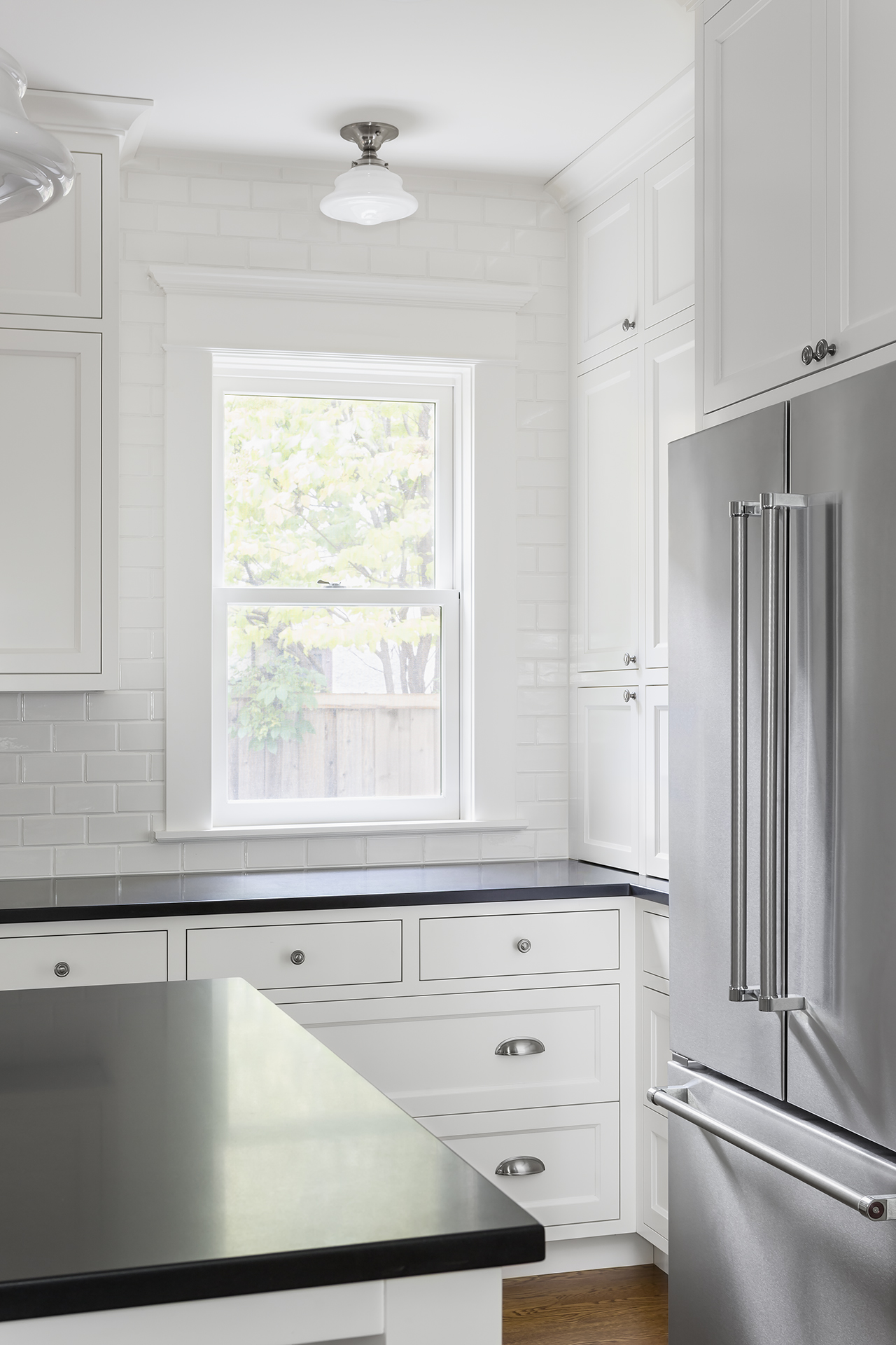 Classic inset doors and drawers, satin nickel hardware and reproduction lighting are nods to the past, while stainless steel appliances, honed-granite countertops and a center island add modern touches.