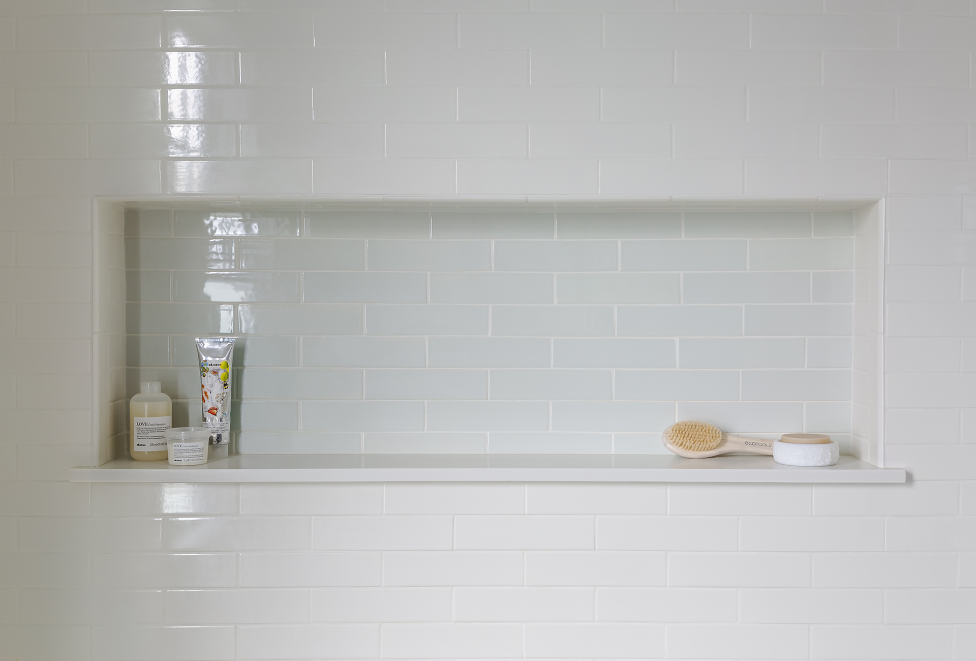 An oversized shower niche with contrasting tile provides ample storage and keeps clutter to a minimum.