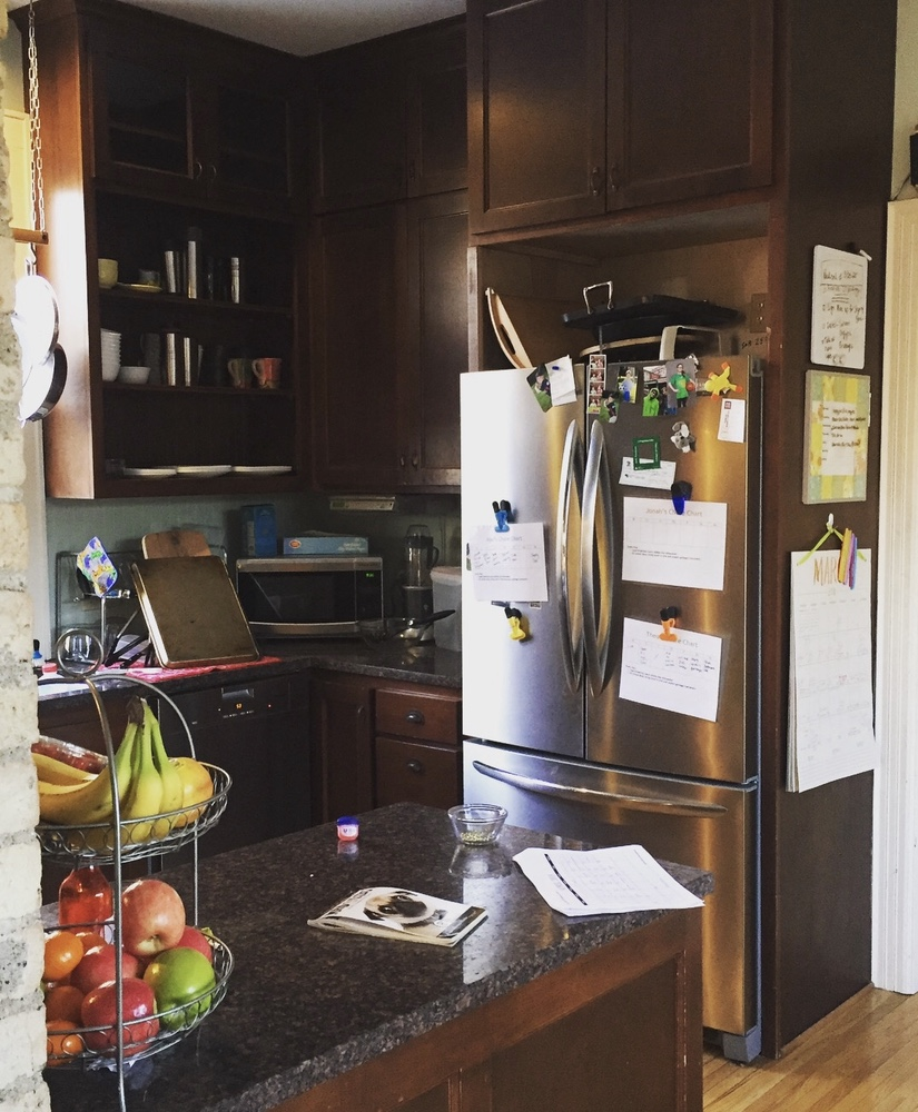 The original kitchen was dimly lit with dated, dark cabinets and a cramped, inefficient layout.