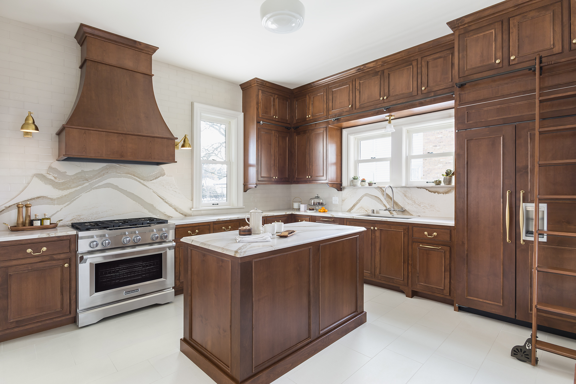 Light-colored floors and backsplash contrast with the darker-stained cabinetry.