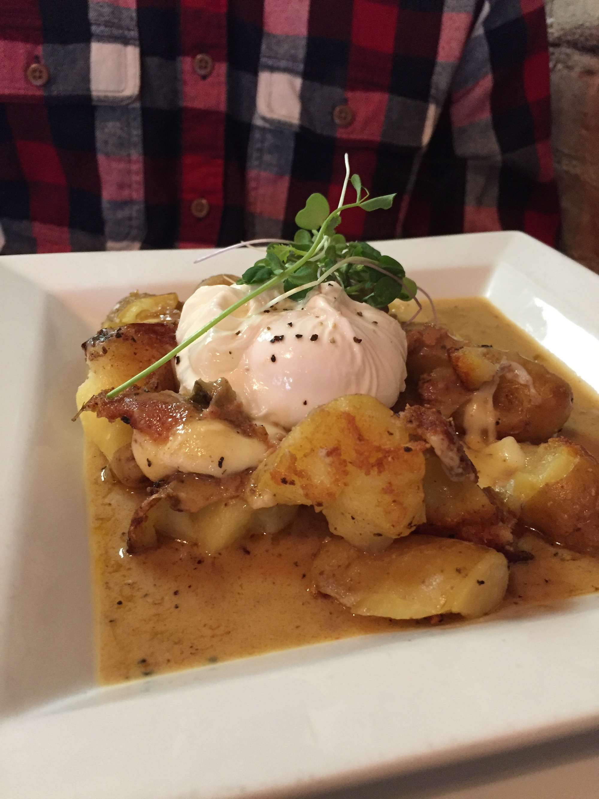 Poached egg with sausage over potatoes