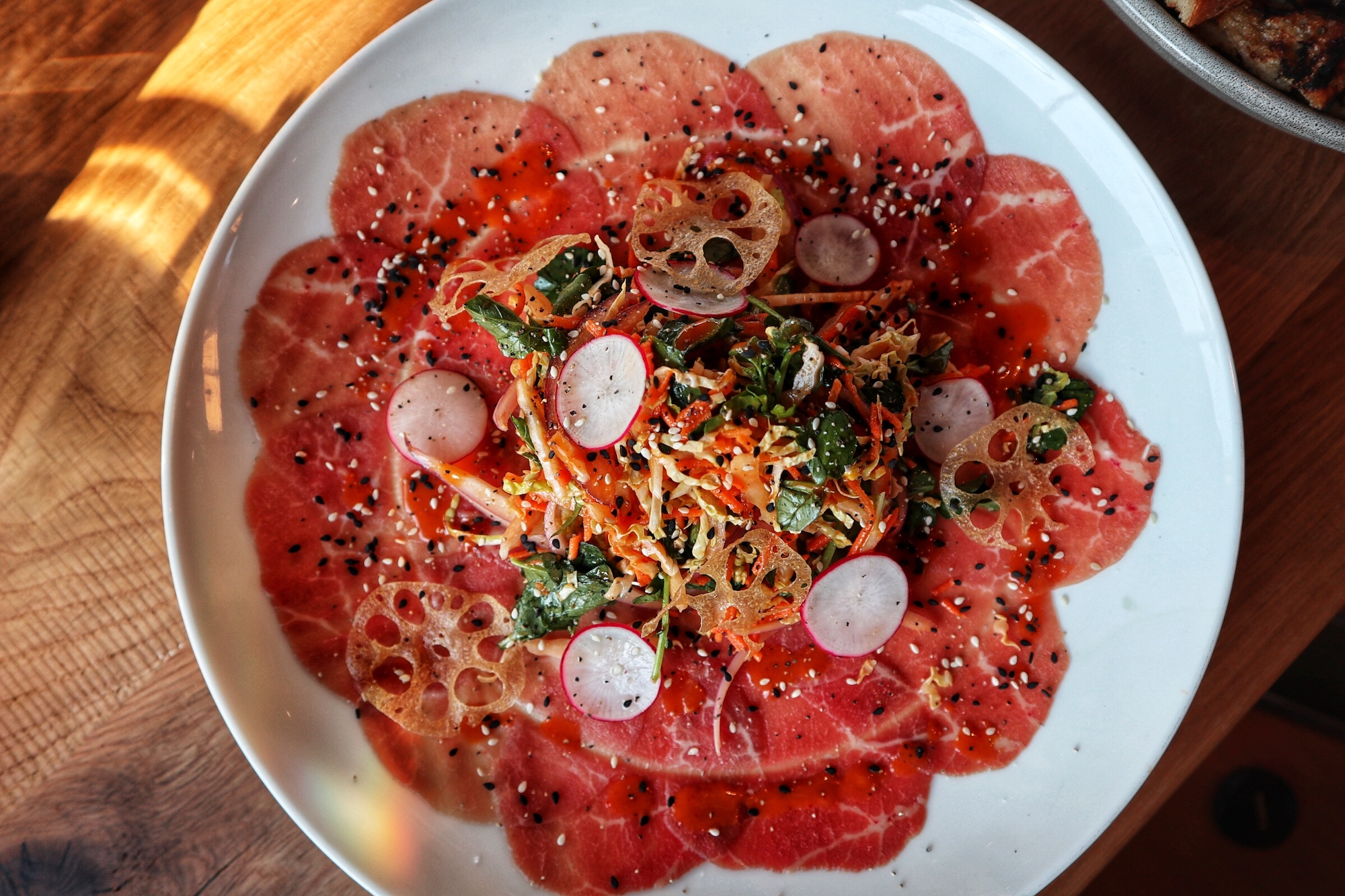 Carpaccio: shaved eye of round, watercress and cabbage slaw, radish, crispy lotus root, with a ponzu vinaigrette