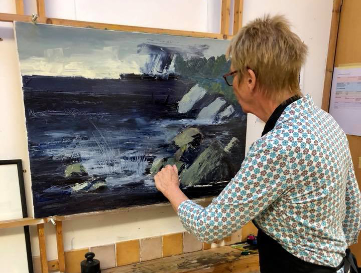 landscape format photo Linda Nevill painting in her studio.jpg