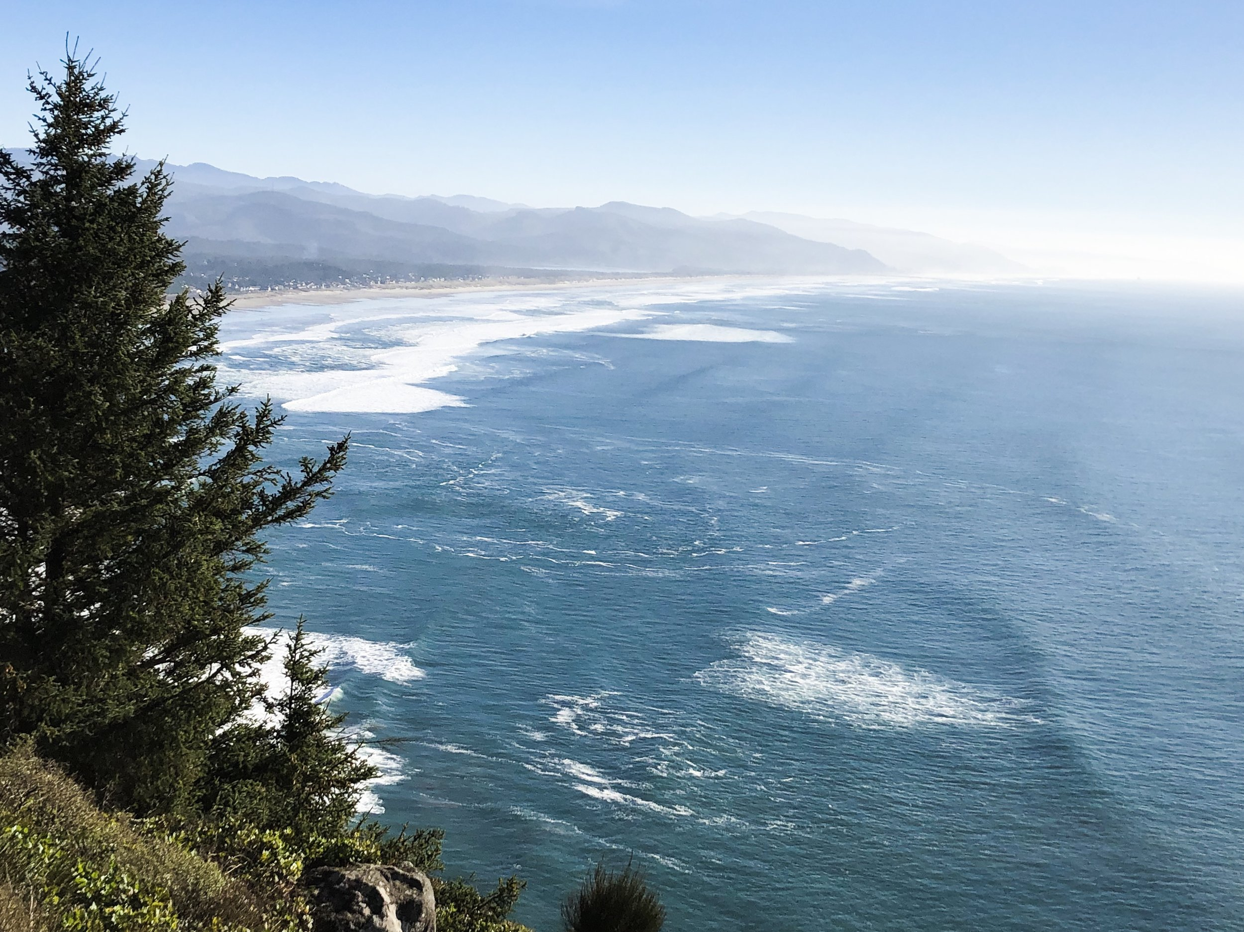 This is a surprisingly common sort of view. From Cape Falcon looking south over Neahkahnie and Nedonna beaches and Cape Meares in the distance