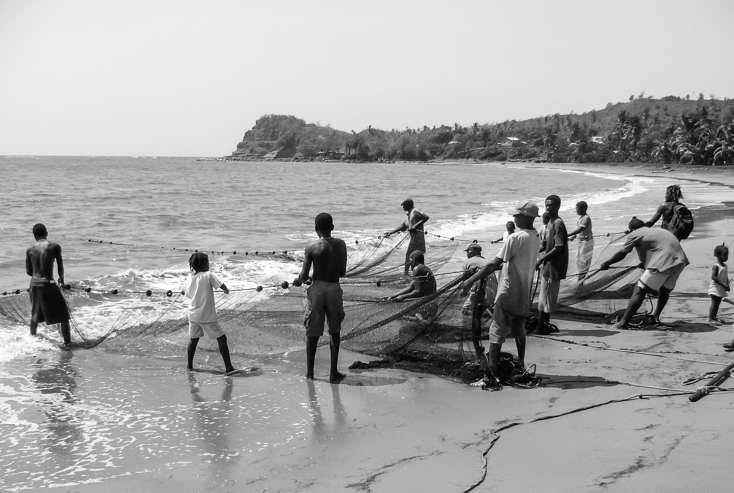 Beach community pulling on drag nets for fish to be sold to tourist restaurants; everyone gets a share of the revenues. It can take a couple of hours of back breaking work to pull in just one net which had been set hundreds of yards out by a boat. Each pull moved the net only by a couple of inches.