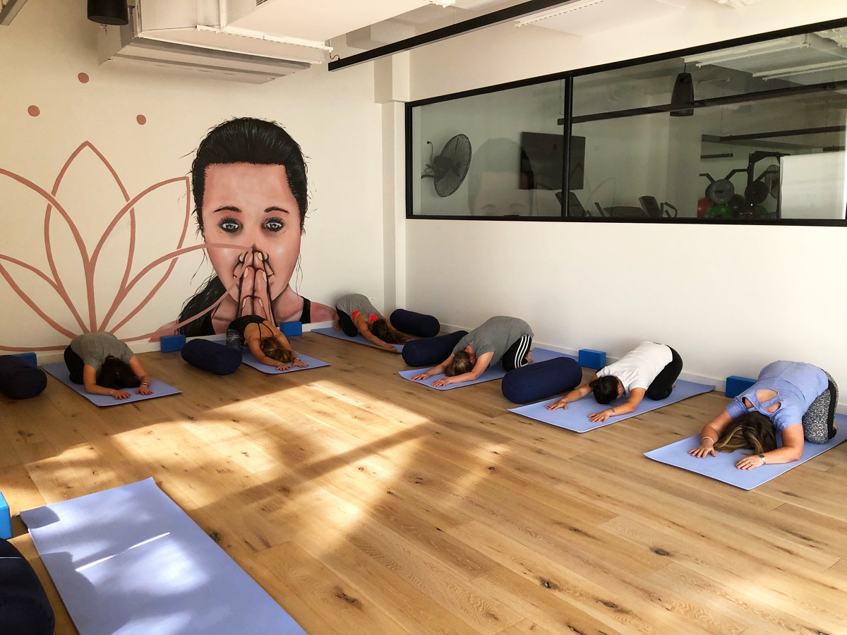 People in yoga studio stretching - Small Circle