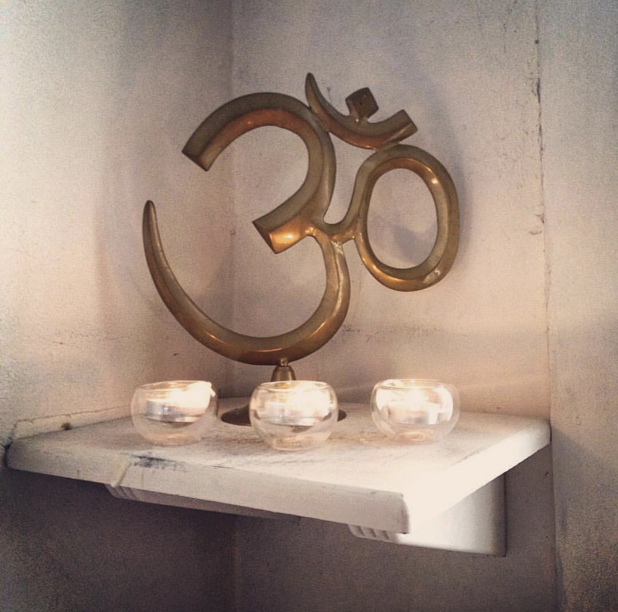 OM symbol statue on table surrounded by candles - Small Circle
