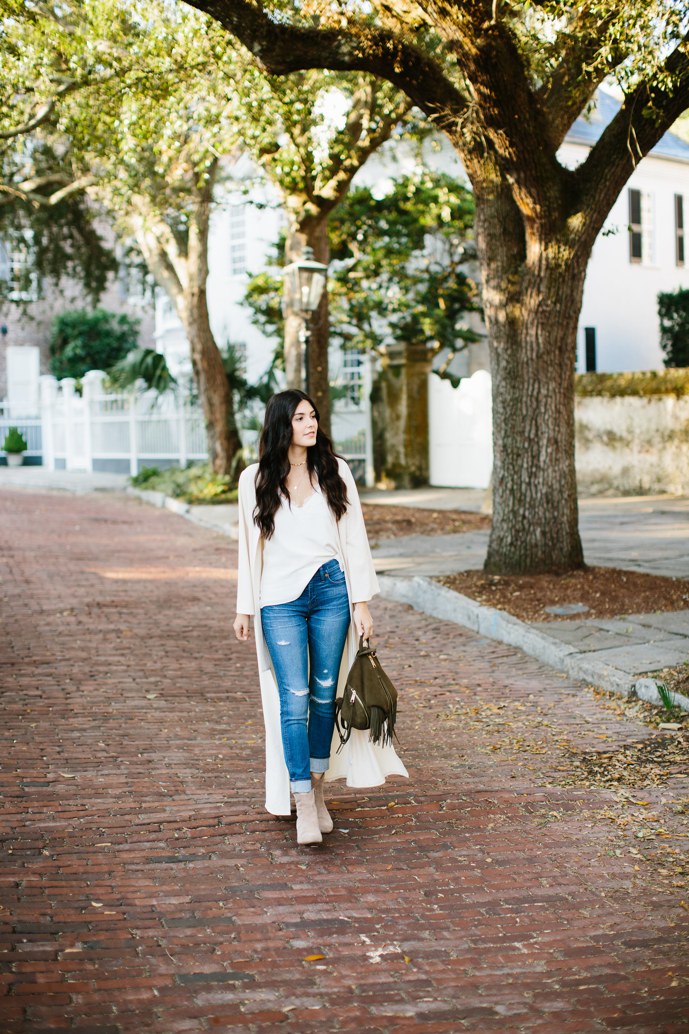 Julia Friedman wearing a Nude Duster Coat Rebecca Minkoff Backpack with Madewell Jeans and Steve Madden Suede Booties and a white lace trim top.