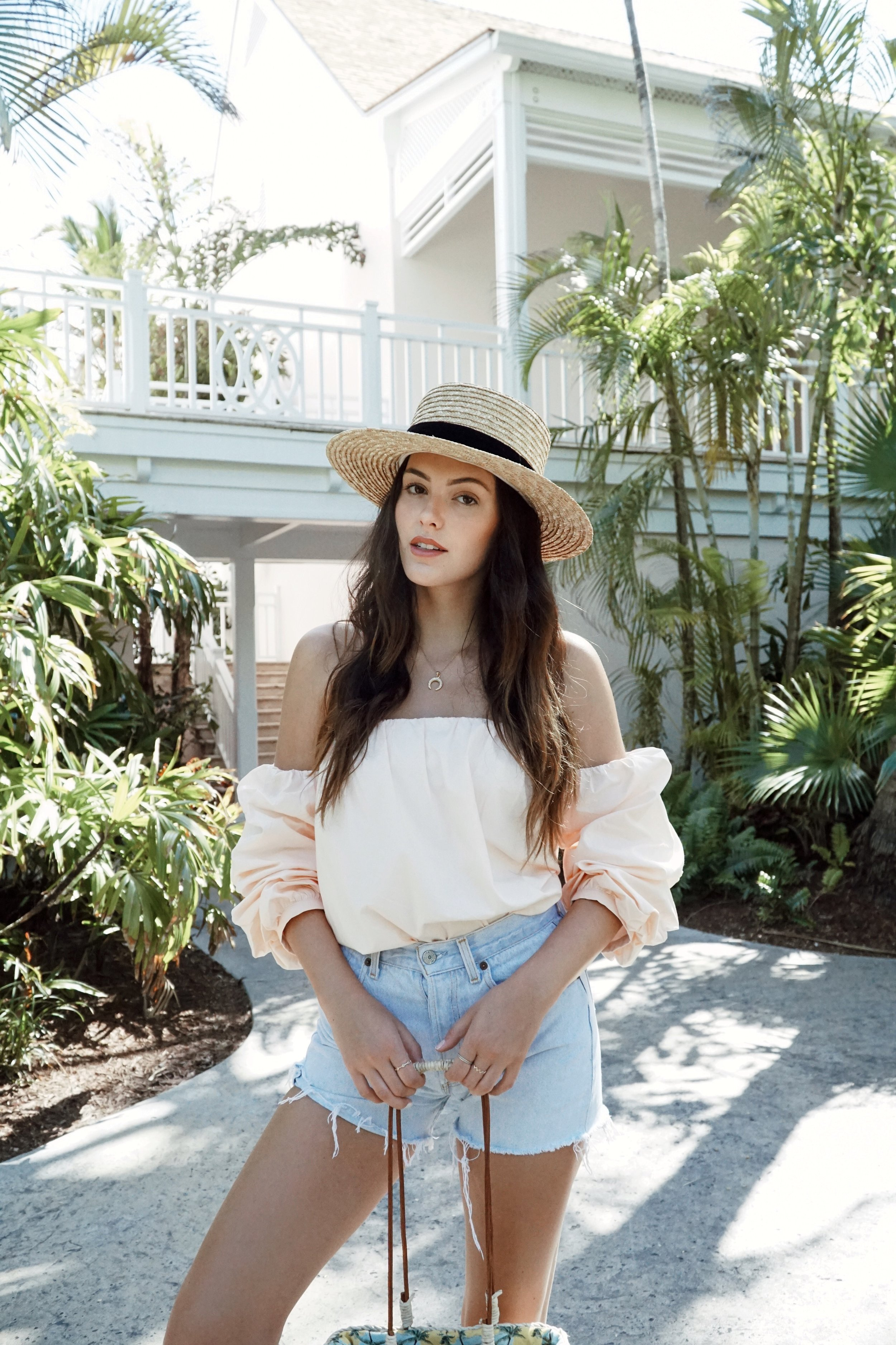 Julia Friedman in a L'academie top, levis jean shorts, and a Lack of Color Spencer Boater hat iat the One&Only Resort in the Bahamas.