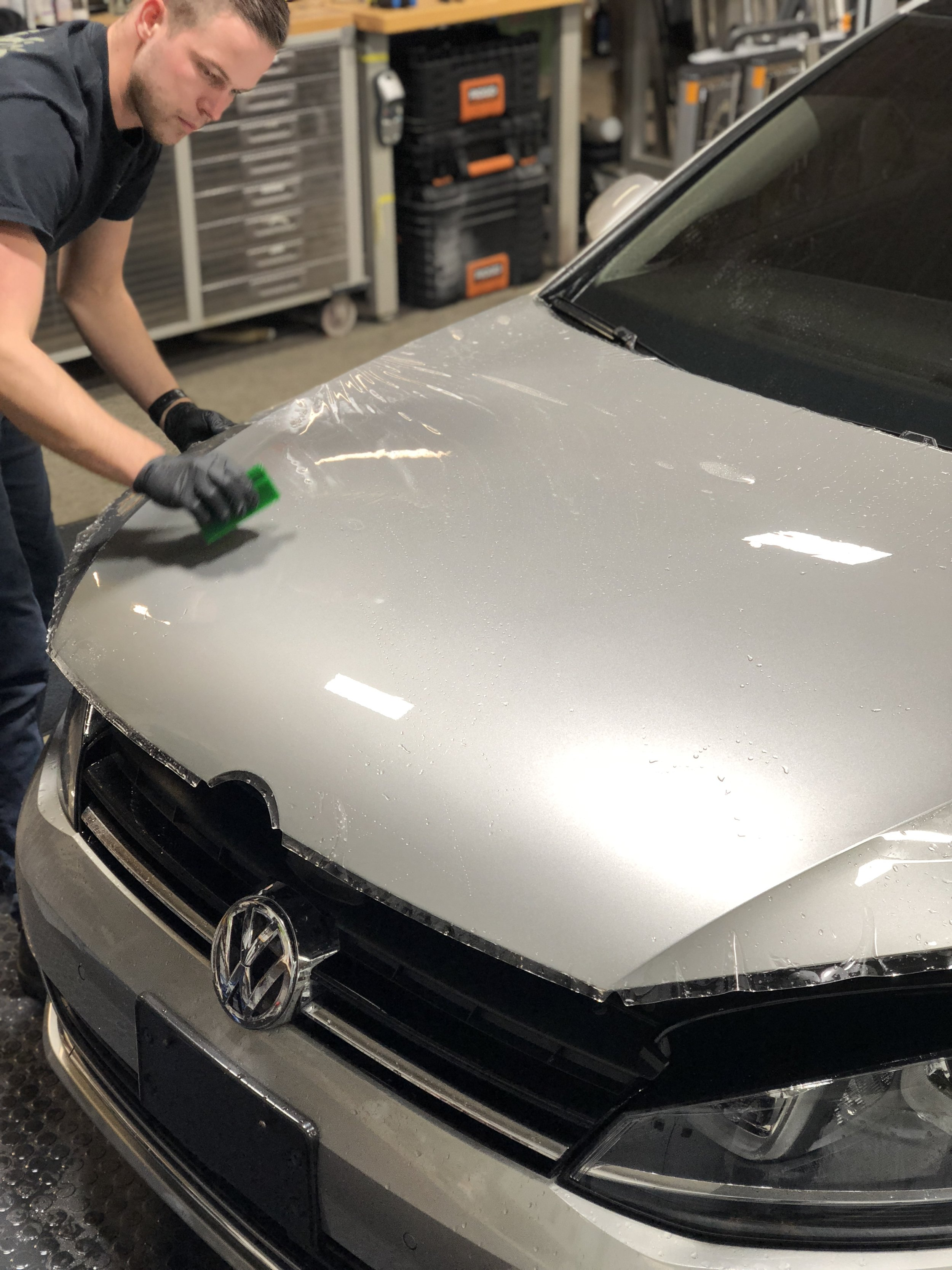 Installer using squeegee to remove installation solution under neath the film - this bonds the film to the body panel.