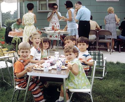 I'm pretty sure this is our family July 4th barbeque at my first childhood house, especially since my dad has the apron on for all the heavy barbecuing being done. That's me at the kids table, back left, and my sister, front right. Gosh, we were cute.