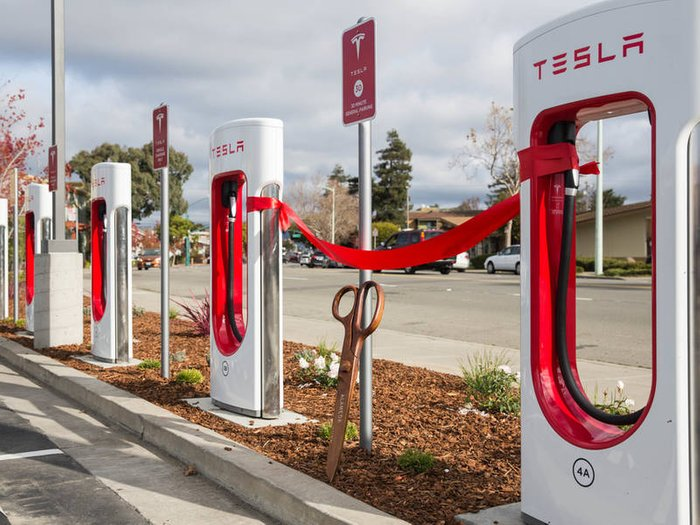 Brand new Tesla chargers await ribbon cutting ceremony with oversized brass scissors leaning against Tesla sign under a red ribbon tied between two of the chargers.