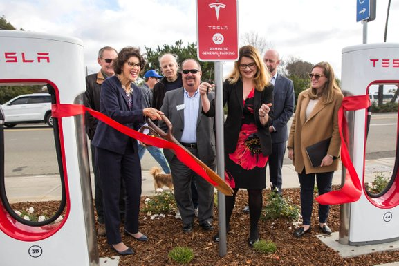 The smiling Mayor of Alameda uses giant brass scissors to cut giant red ribbon tied between two brand new Tesla chargers at South Shore Center surrounded by smiling people.