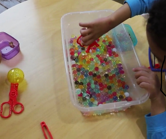 An example of a child playing with  Li'l Gen Water Bead  to develop pre-scissor skills.