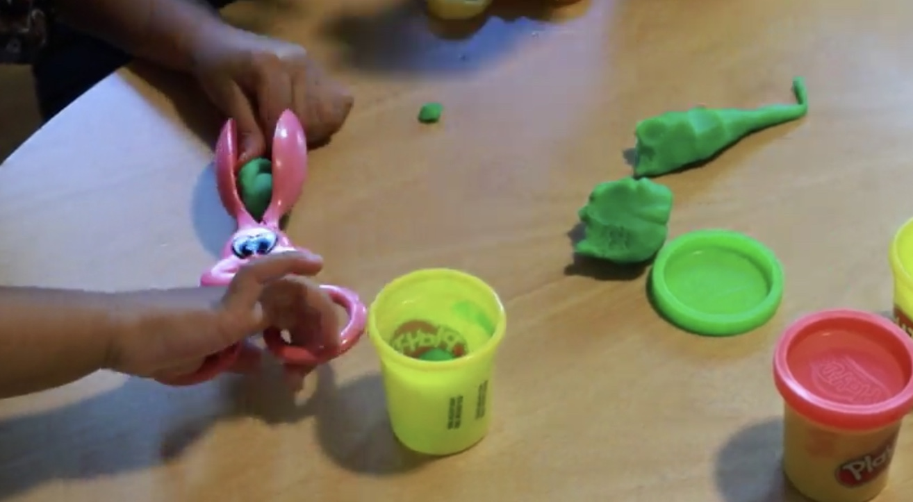 A child using  Fun Shaped Easter Bunny Egg Dipper Scissor Tong  and  Play-Doh  to practice pre-scissor skills.