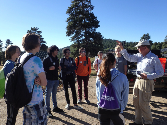 Tim Seastedt (right) and student volunteers discuss ecosystem services and the task at hand before working on a restoration project.