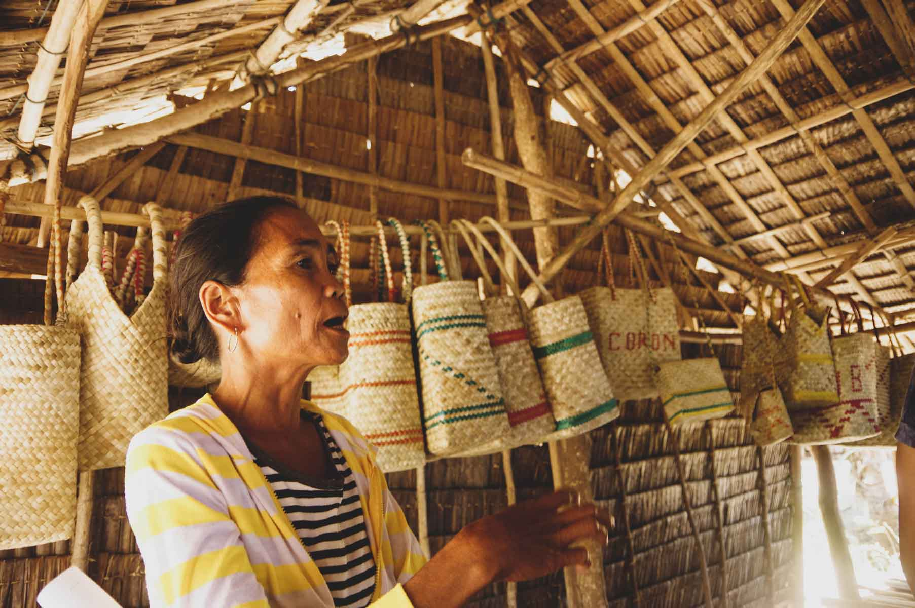 A member of the Sékéd Weavers Association introducing the variety of products and patterns they create and sell.