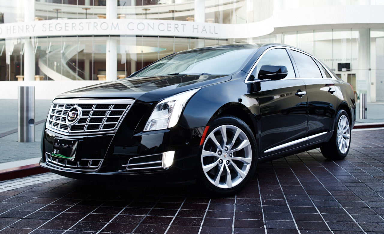 STANDARD: Cadillac xts - Complimentary water. WiFi available upon request. Seats up to 3 passengers with three pieces of luggage.