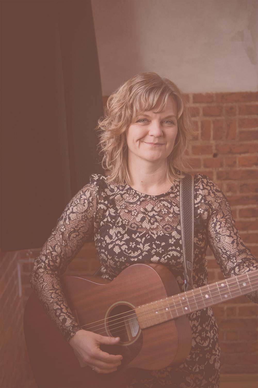 Sort hvidt portræt af Sangerinden Christina Dahlerup stående med sin guitar i modlys. Fotograf: Tam Vibberstoft.