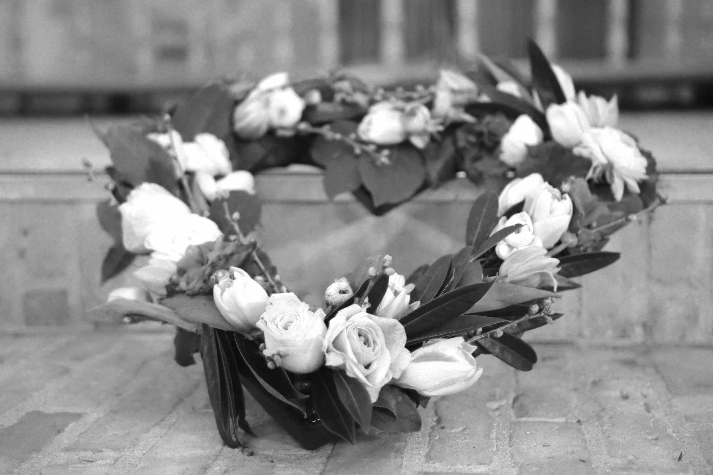 Foto af hjerteformet blomsterkrans med røde og pinke roser lagt på kirkegulv.. Yndlingssangen giver ceremonien en smuk sidste afsked.