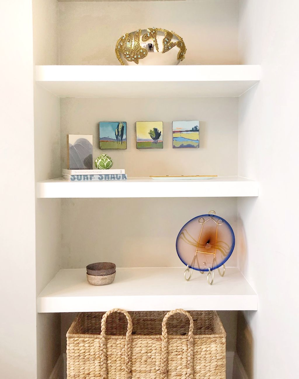 This was an empty niche. Substantial shelving was custom built on site to create a place to display the clients curated pieces we selected for them.