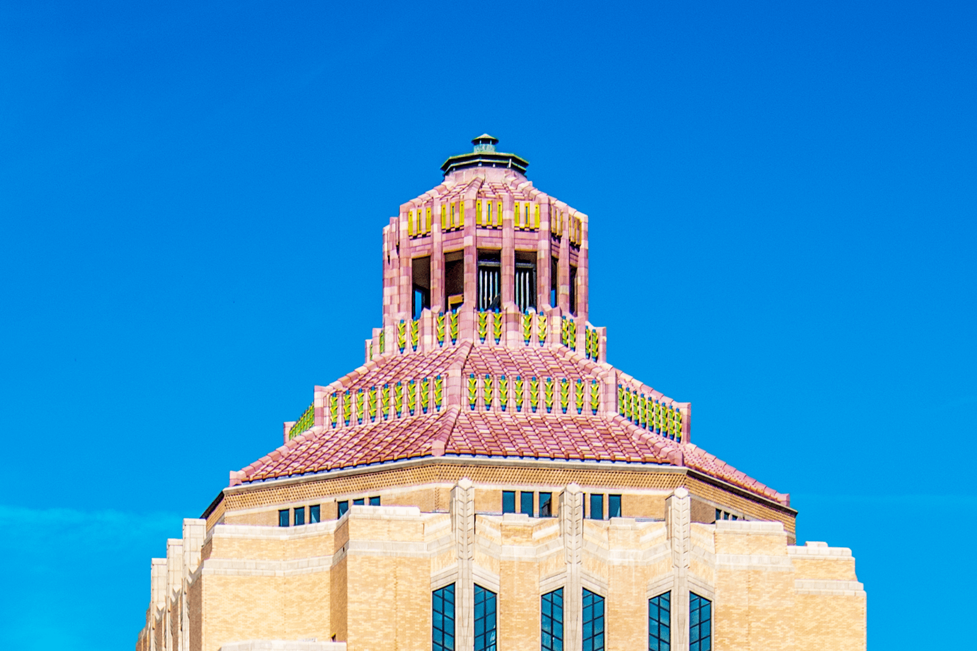 Each roof segment connects through a vertical band, each with green, blue and gold highlights. Douglas Ellington's signature feather-like ornaments can be found on several areas of the façade.