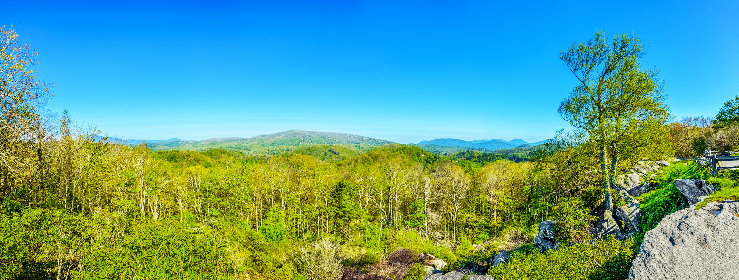 Raven Rocks Overlook  faces  Flat Top Mountain  with an elevation of 4,469 feet (1,362 meters). To the west of  Flat Top Mountain  slightly behind the trees is  Calloway Peak , the highest point of  Grandfather Mountain  with an elevation 5,964 feet (1,817 meters). To the east of  Flat Top Mountain  are  Snakeden Mountain  (4,485 feet - 1,367 meters),  Rich Mountain  (4,746 feet - 1,447 meters),  Snake Mountain  (5,568 feet - 1,697 meters) and  Elk Knob  (5,520 feet - 1,682 meters).