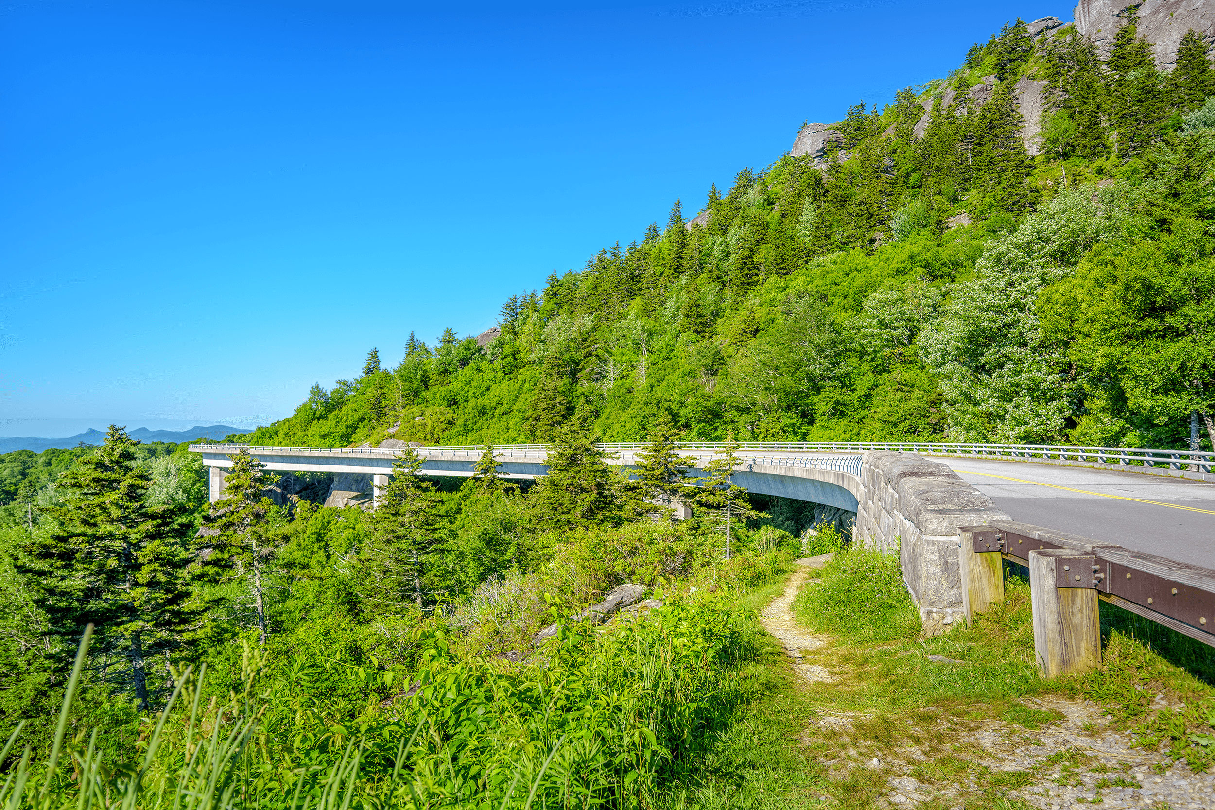The  Linn Cove Viaduct  rests on seven giant concrete footings and follows in snake-shape form the contours of  Grandfather Mountain  without touching the slopes of  Grandfather Mountain , making the viaduct an engineering marvel and one of the most photographed attractions along the Blue Ridge Parkway.