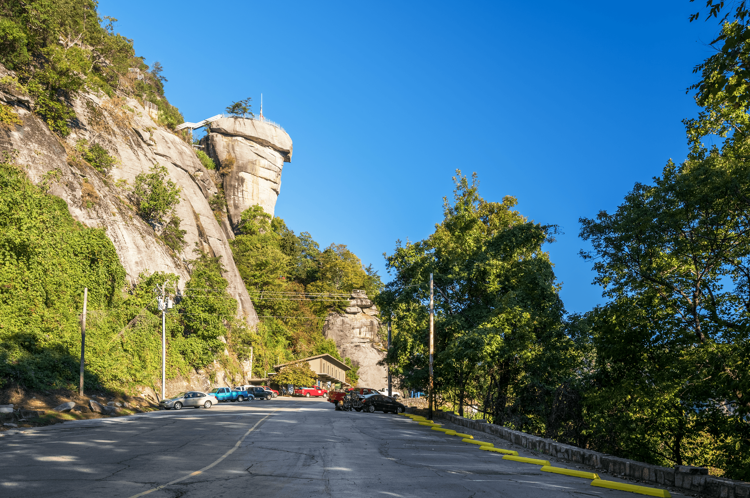 When you arrive at the parking area of  Chimney Rock Park , you are greeted by the mighty  Chimney Rock  towering high above the granite cliff.