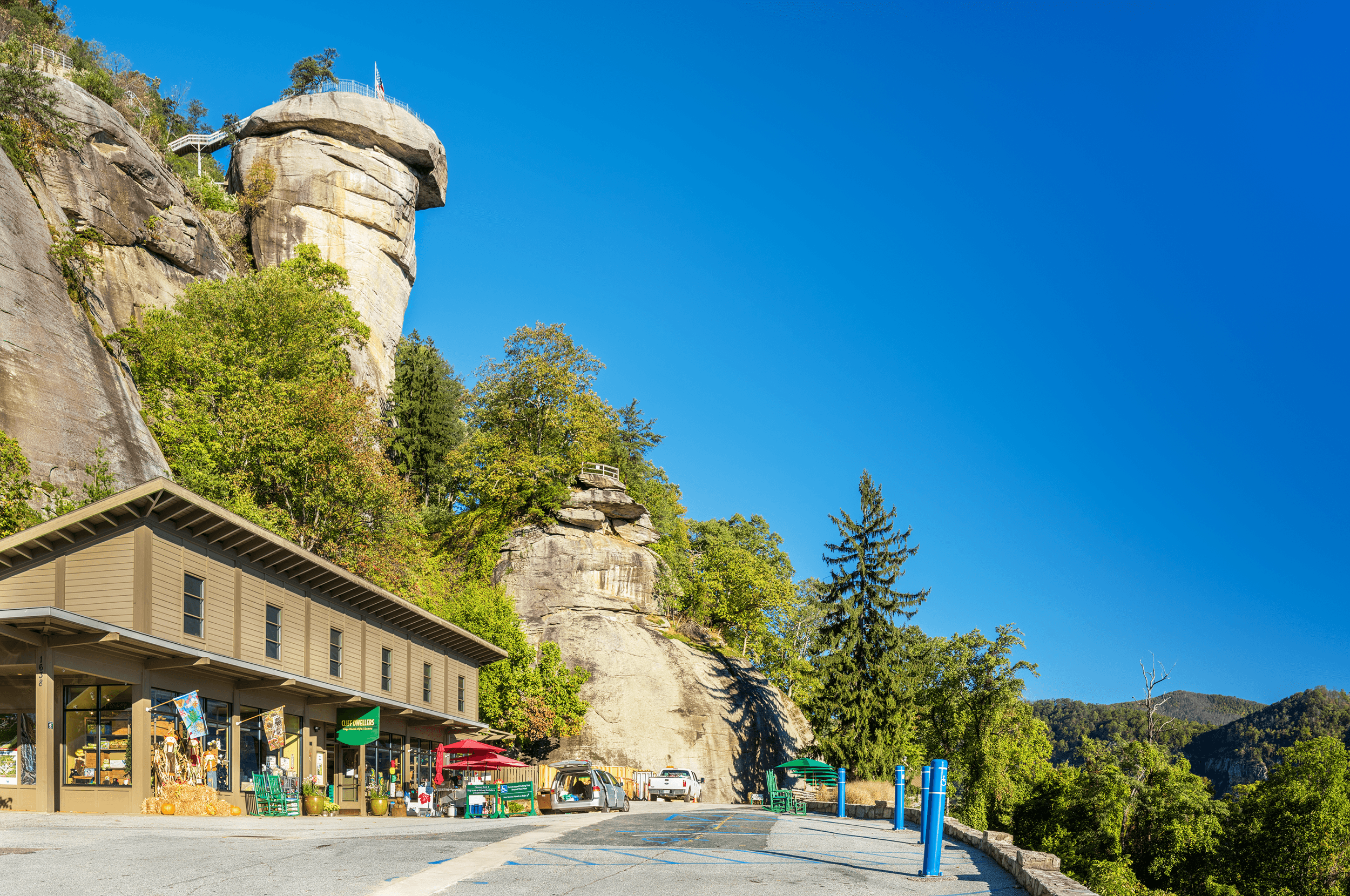 The  Cliff Dwellers  is a gift shop, and to its left is a 198-foot tunnel leading to the lift that brings you to the  Sky Lounge . The 26-story elevator shaft was blasted through solid rock. You can also take the  Outcroppings Trail , which starts passed the gift shop and leads to the top of  Chimney Rock  through a network of stairs. Should you prefer to take the elevator, please call ahead to confirm that it is operational during your planned visit.