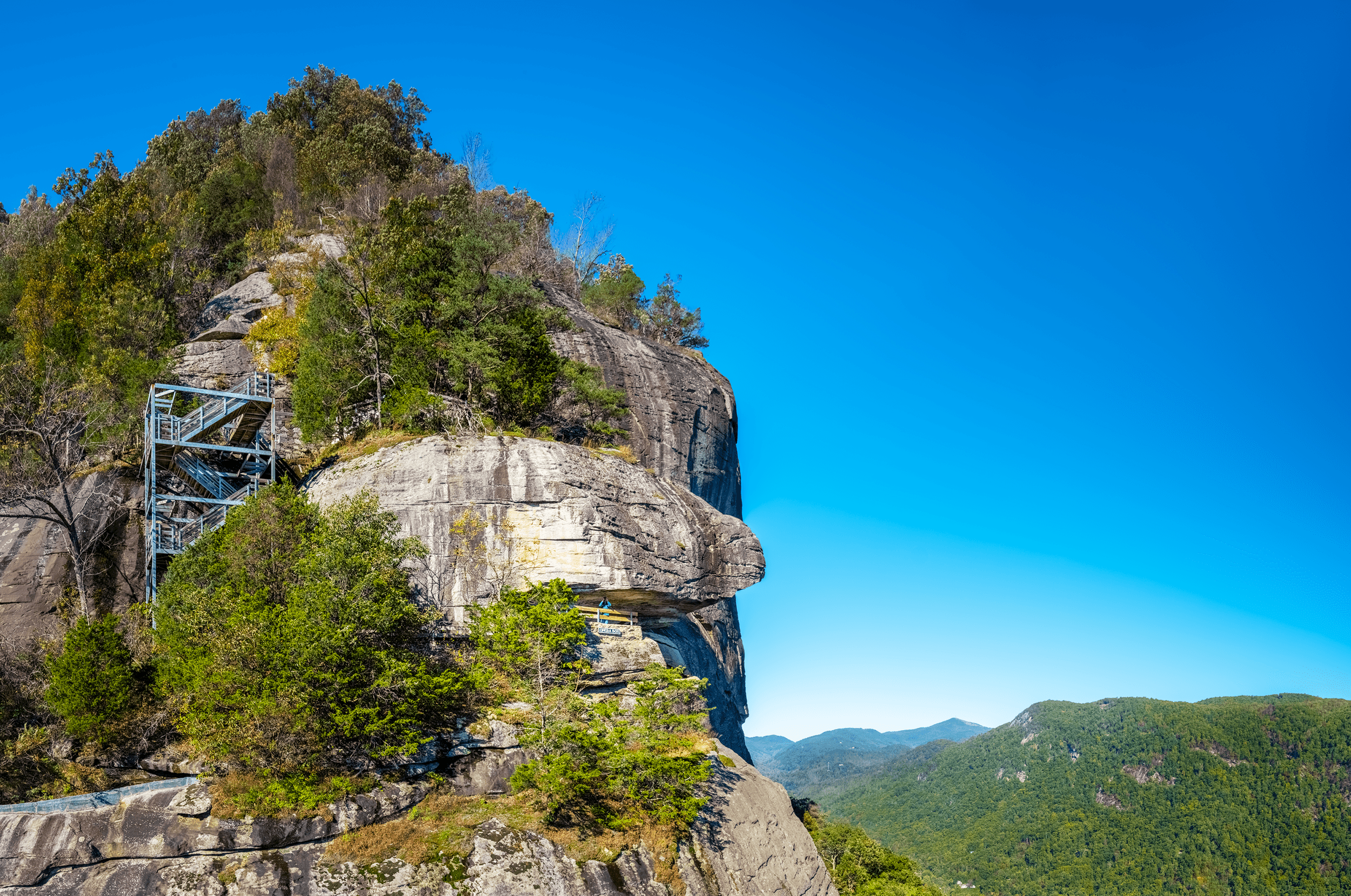 Behind  Chimney Rock  is the famous  Opera Box  covered by an imposing rock overhang. The staircase to the left is part of the  Exclamation Point Trail , which connects to the  Skyline Trail .