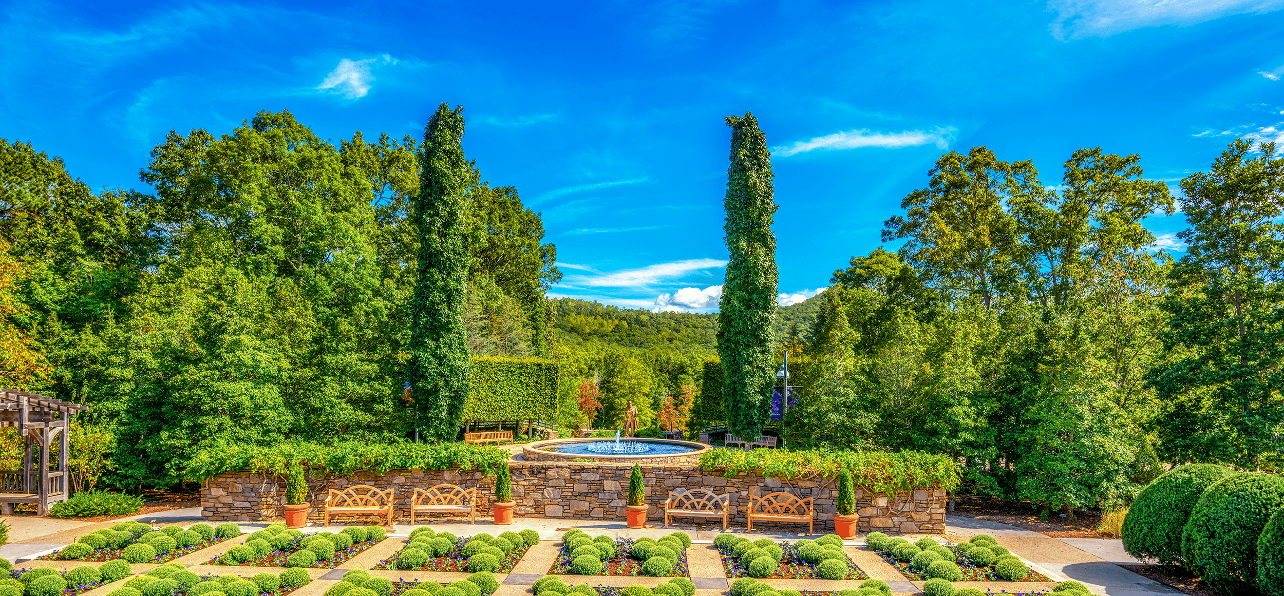 American landscape architect Frederick Law Olmsted originally envisioned the  North Carolina Arboretum  in 1898, shortly after he finished the beautiful grounds on  Biltmore Estate  in Asheville, which include  The Gardens at Biltmore House . Pictured here are the lovely  Quilt Garden  and the  Blue Ridge Court  with its water fountain and the 8-foot bronze statue of Frederick Law Olmsted. The statue was sculptured by Zenos Frudakis in 2016, representing Frederick Olmsted during his time in Asheville.