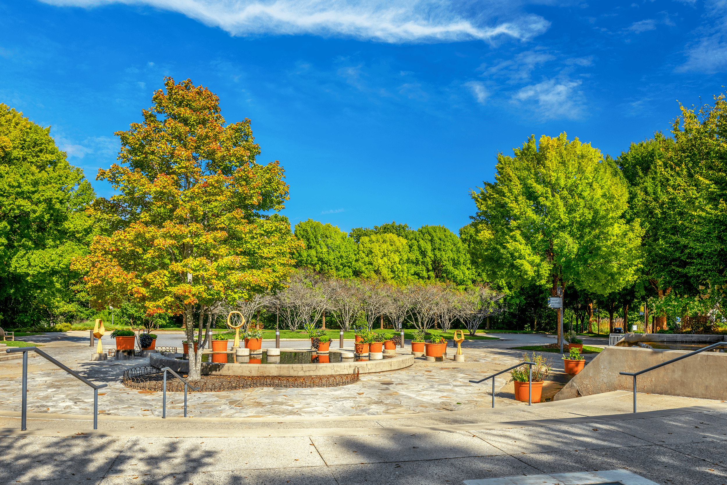 View from the  Entrance Plaza  by the  Education Center . Three art pieces, called  Magniflowers , surround the water pool at the center of the plaza. Also located in the  Education Center  is the  Savory Thyme Café .