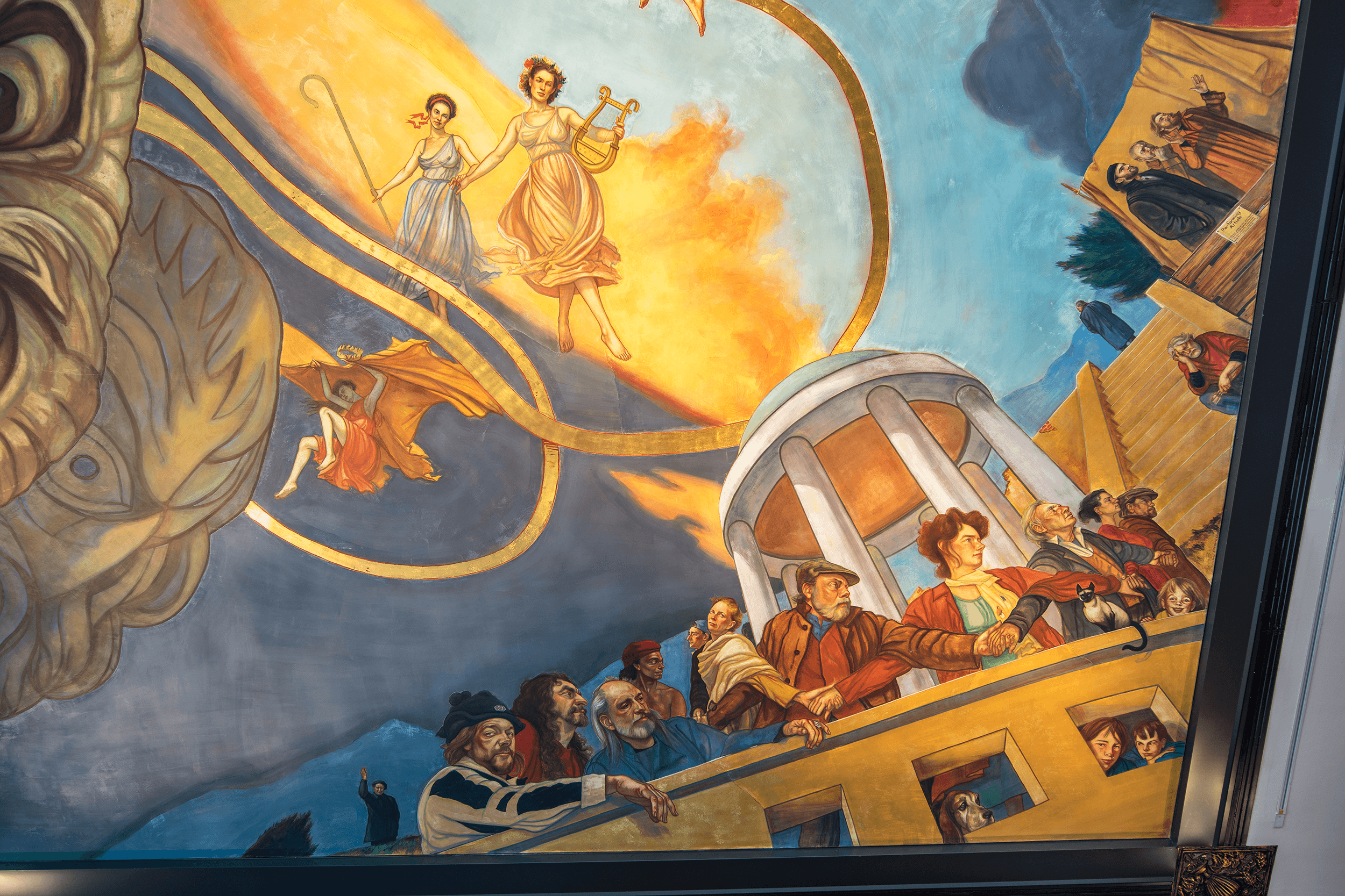 Ben Long, typically, closely models the faces in his frescos on those of his family, colleagues, and friends. The golden ribbon that flows throughout the fresco is the ribbon of life and is made of 22-karat gold leaves.