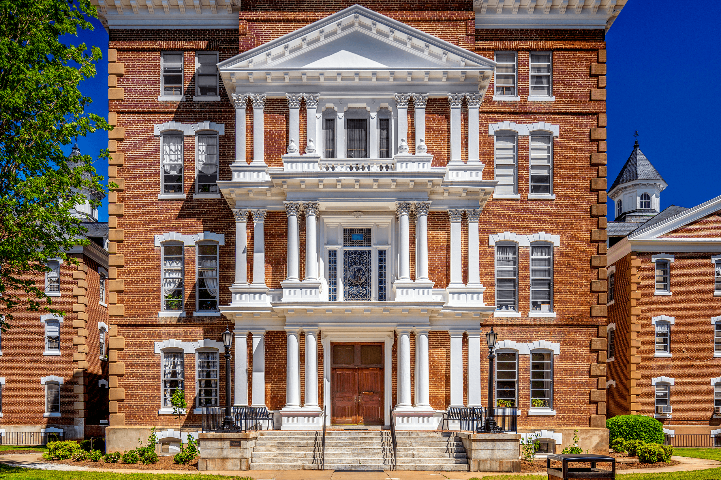 Acclaimed Philadelphia architect Samuel Sloan (1815-1884), who was known for his hospital and public building designs, developed the plans for the Broughton Hospital complex in 1875. The large, three-story portico has paired Roman Doric columns on pedestals, flanking the entrance. The second level of the portico has Corinthian columns, while the third level uses paired urns instead of columns.