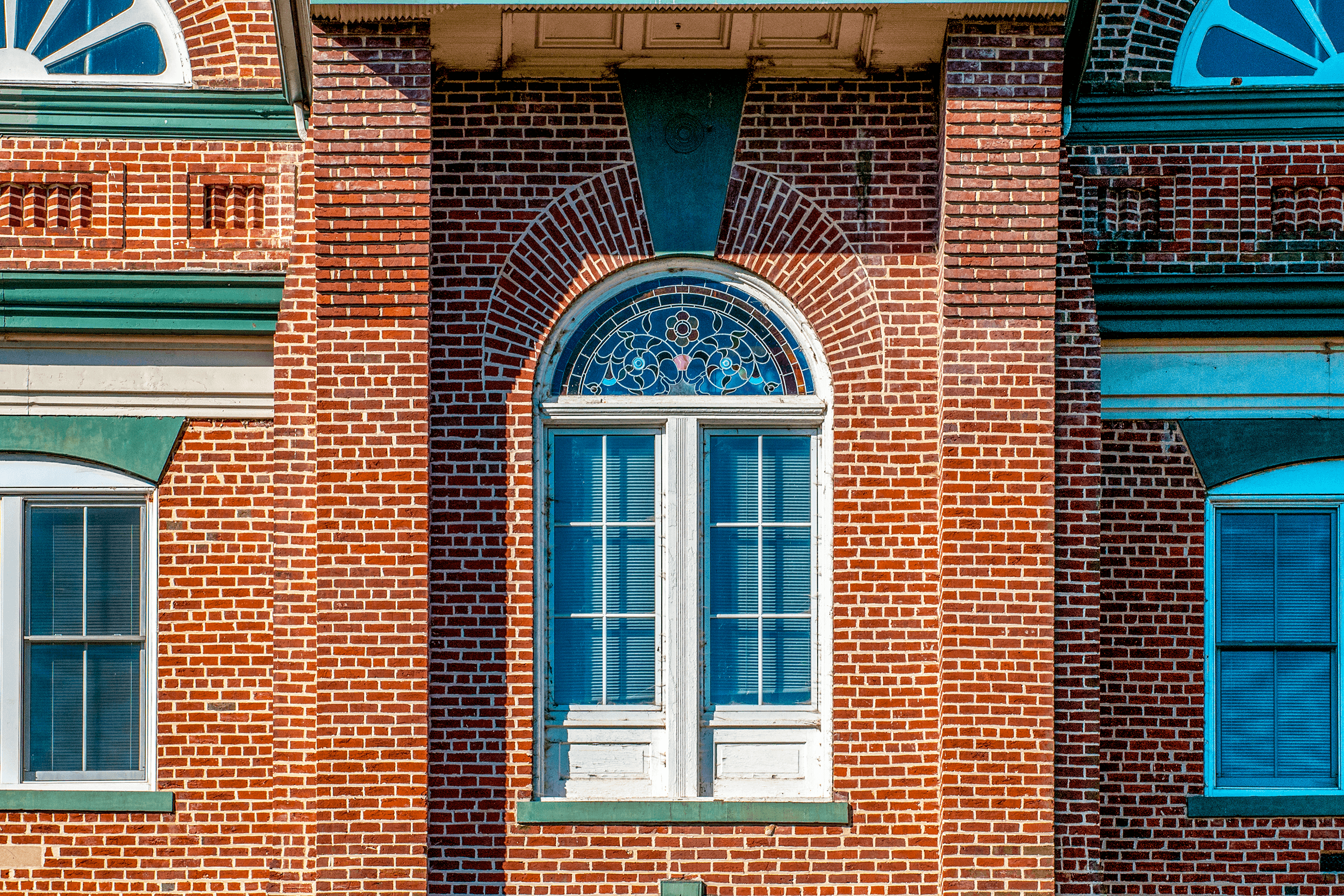 Small details. Here a false door with a stained glass fanlight under the balcony at the clock tower.