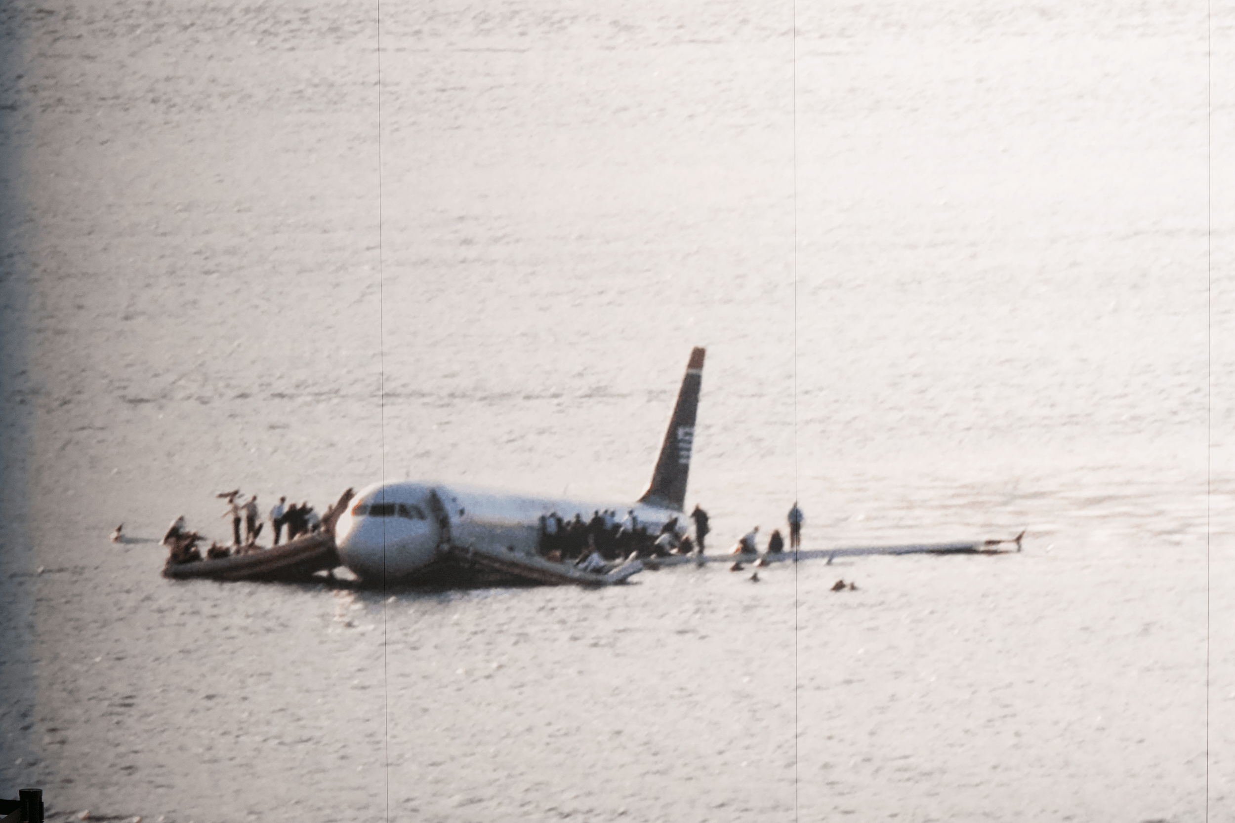 """Just three minutes after both engines had lost power, the plane hit the water near midtown Manhattan. Several passengers suffered injuries, a few of them severe, but only one passenger required overnight hospitalization.   Original picture """"Plane crash into Hudson River"""" by Greg Lam Pak Ng, Flickr, licensed under Creative Commons CC BY 2.0, cropped."""
