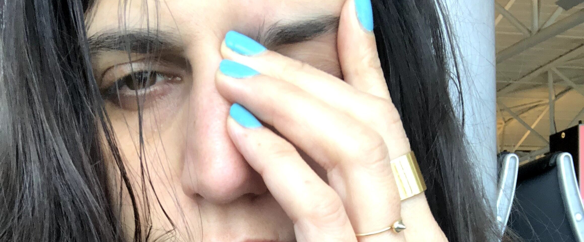 A picture I took of myself with my hand over my left eye, the one that always gets the migraines behind it, looking squinty and kind of pathetic. But wearing some good rings and turquoise nail polish.