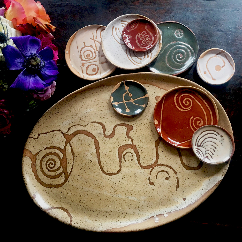 "large platter with créme brûlée on speckled clay accompanied by assortment of 5"" & 3"" plates"